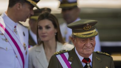 Spanish Crown Prince Felipe, background left, talks with Spanish Princess Letizia, as then Spanish King Juan Carlos, foreground looks on, during a military parade on Armed Forces day in Madrid, Spain (photo: June 8, 2014)