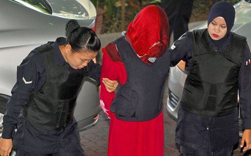 Vietnamese Doan Thi Huong, centre, is escorted by police as she arrives for a court hearing at Shah Alam High Court in Malaysia. (AP).
