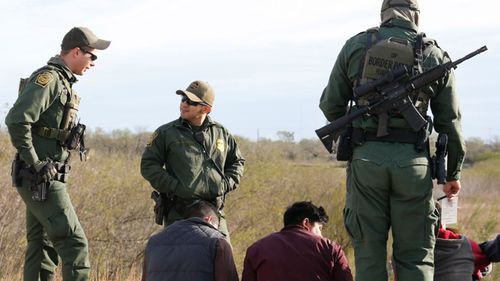 US border agents in Texas  hold suspected migrants who made an unauthorised crossing from Mexico.