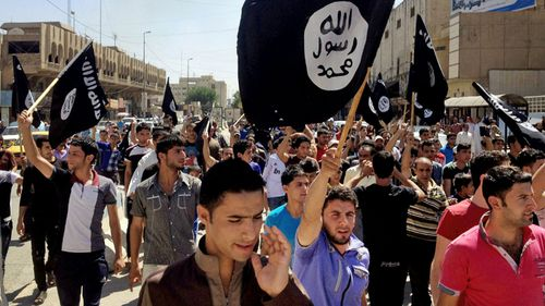 Islamic State supporters march through the streets. (AP)