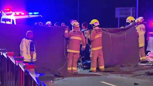 Firefighters work with NSW Ambulance paramedics to assist the injured women.