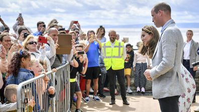 Britain's Prince William and Kate, the Duchess of Cambridge talk with members of the public in Barry Island, Wales, Wednesday Aug. 5, 2020, during their visit to speak to local business owners about the impact of COVID-19.