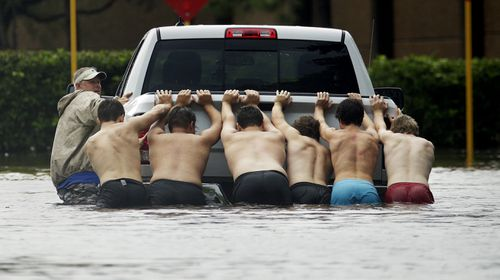 People push a stalled pickup to through a flooded street in Houston. (AP)