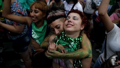 Abortion-rights activists celebrate as Argentine lower house approves a bill that would legalise abortion outside Congress in Buenos Aires, Argentina, Friday, Dec. 11, 2020