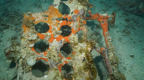 The punched holes of the split-panel dive brakes from an SBD-5 Dauntless dive bomber are visible resting on the floor of the lagoon near the main debris site.