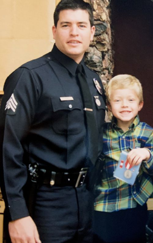 Detective Tim Shaw pictured with his son Tyler, who holds the Los Angeles Police Department medal his father was awarded for his role in the 1997 North Hollywood shootout.