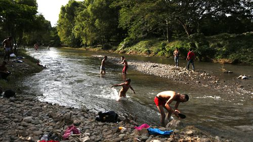 Migrants bathe and wash clothes in the Novillero River as a caravan of Central Americans trying to reach the US border halts for a rest day in San Pedro Tapanatepec, Oaxaca state, Mexico.