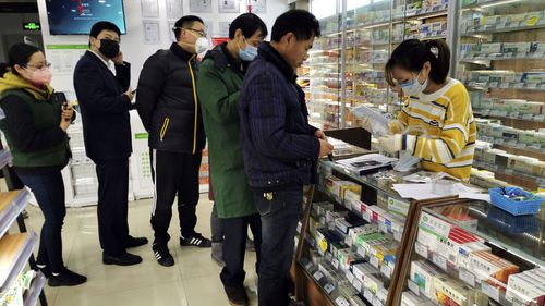 People line up to buy face masks at a pharmacy in Shanghai, Monday, Jan. 27, 2020.