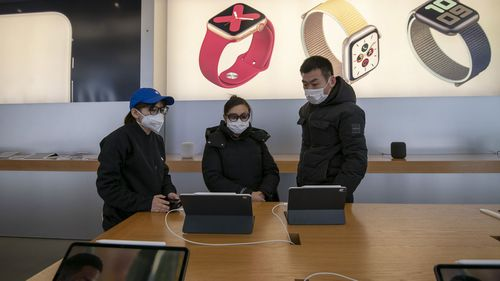 A female sales person in a blue baseball cap with an Apple logo and a protective mask shows iPads to a male and female couple insdie the Apple Store in the Xintiandi commercial precinct.