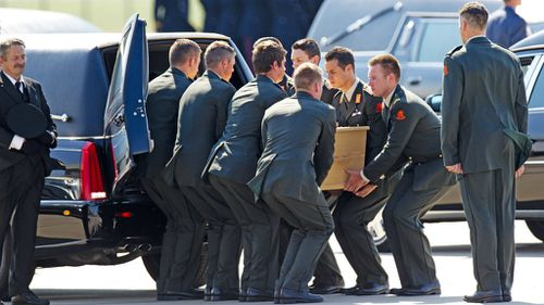 Dutch military personnel load a numbered coffin, contraining an unidentified body from the crash of MH17, into its own hearse at Eindhoven airport. (Getty)