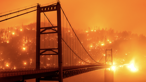 Seen in a long exposure photograph, embers light up a hillside behind the Bidwell Bar Bridge as the Bear Fire burns in Oroville, Calif., on Wednesday, Sept. 9, 2020. (AP Photo/Noah Berger)