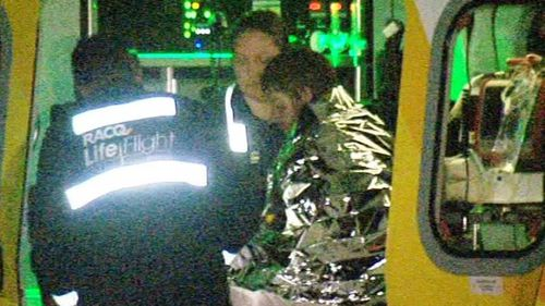 Paramedics tend to injured father Nathan Perry after the fire. (WIN News)