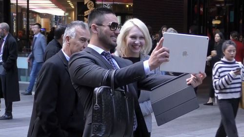 Salim takes a selfie with a passer-by outside court. Picture: 9News