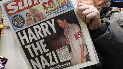 """<b>Nazi outfits:</b> In 2005, photos surfaced of Prince Harry wearing a swastika armband to a fancy dress party. Clarence House was forced to apologise for his bad judgement as Jewish communities labelled the outfit """"poor taste"""". (AP Photo)"""