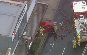 Car catches fire after crashing through window in east Melbourne, road closed