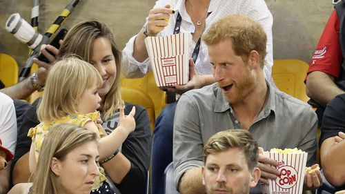 Hayley Henson and daughter Emily Henson sit with Prince Harry at the Sitting Volleyball Finals during the Invictus Games 2017. (AFP)