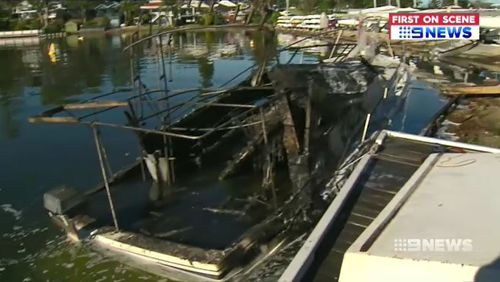 The boat's charred wreckage remains moored at the yacht club. Picture: 9NEWS.