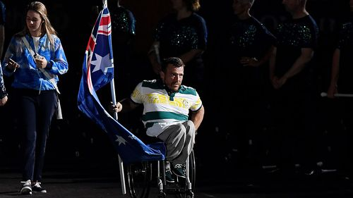 Flagbearer Kurt Fearnley enters the stadium before the start of the closing ceremony, a moment television viewers at home missed out on seeing. (AAP)