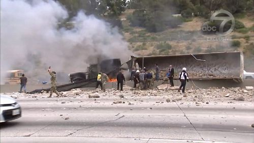 A truck carrying cement collided with a sedan and overturned on the 405 freeway (9NEWS)