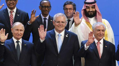 Scott Morrison waves to the camera next to Russian President Vladimir Putin and Saudi Crown Prince Mohammed Bin Salman.