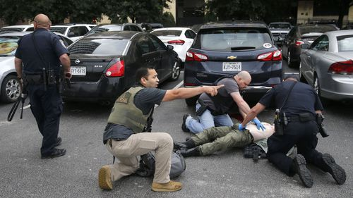 Members of the Department of Homeland Security and the US Marshal's Service tend to the downed shooter after shots were fired.