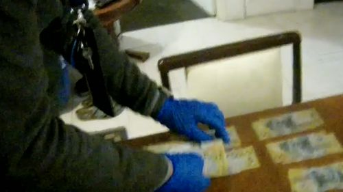 Police found more than $8,000 in cash in the man's kitchen, allegedly the proceeds of crime.
