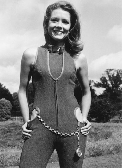 English actress Diana Rigg wearing a violet-coloured catsuit with cut-away hips, one of her costumes from the new series of 'The Avengers', 5th September 1966