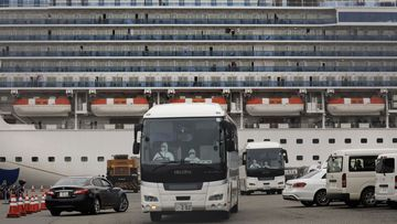 An ambulance leaves Yokohama Port where the Diamond Princess, back, is docked in Yokohama, near Tokyo, Friday, Feb. 14, 2020. The cruise ship is still carrying nearly 3,500 passengers and crew members under quarantine until at least Feb. 19.