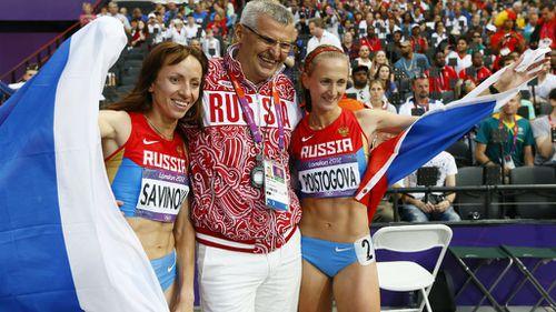 Mariya Savinova (L) and Ekaterina Poistogova (R) of Russia celebrate with Russian coach Vladimir Kazarin in London in 2012. (AAP)