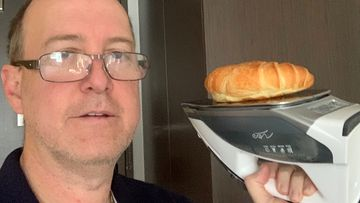 The Sydney dad heats up a croissant on an iron, while he is stuck in quarantine.