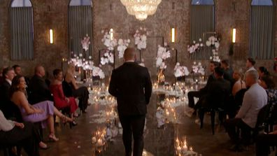 A groom walks down down the aisle to await his bride. There are candles on the floor and an oversized chandelier overhead, creating spectacular, opulent lighting.
