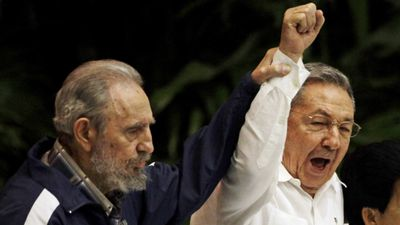 In this April 19, 2011 file photo, Fidel Castro, left, raises his brother's hand, Cuba's President Raul Castro, centre, as they sing the anthem of international socialism during the 6th Communist Party Congress in Havana, Cuba. (AAP)