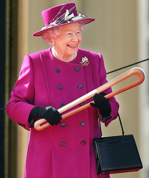 The Queen holds the baton at the relay ceremony at Buckingham Palace. (AAP)