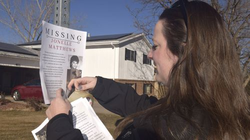 In this December 2018 photo, a victims advocate in Greeley, Colorado posts a flyer of a missing persons poster for Jonelle Matthews.