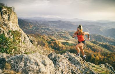 Woman athlete running up mountain