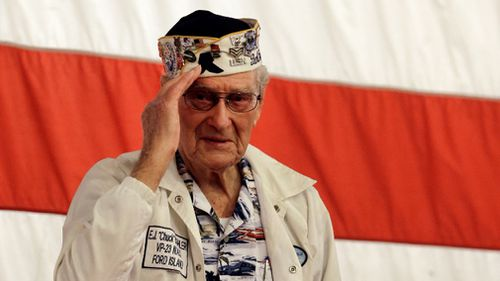 Pearl Harbor survivor Chuck Kohler salutes the audience after giving his remarks during a remembrance ceremony. (AAP)