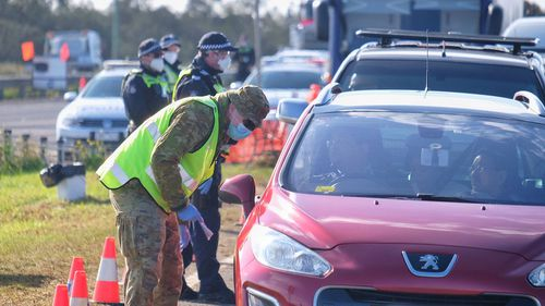 Members of the ADF and Victoria Police work together at a vehicle checkpoint along the Princes Freeway near Little River.