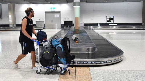 A man walks past an empty baggage carousel at Brisbane Airport.