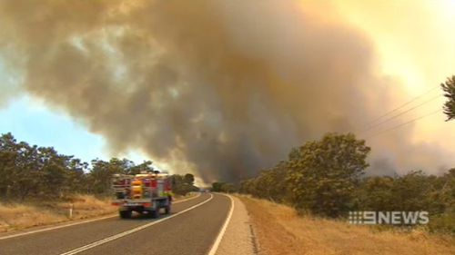 A fire truck races towards the plume of black smoke billowing from the fire. (9NEWS)