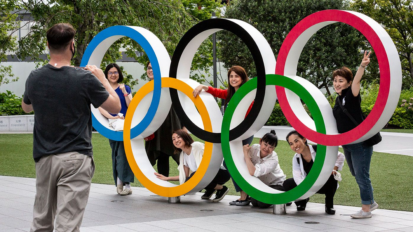 People have their photographs taken next to the Olympic Rings in Tokyo, Japan.