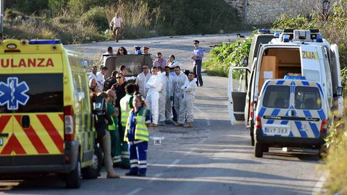 An ambulance is parked along the road where a car bomb exploded killing investigative journalist Daphne Caruana Galizia.
