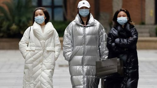 Women wearing protective masks to prevent the new coronavirus outbreak walk on a re-opened commercial street in Wuhan