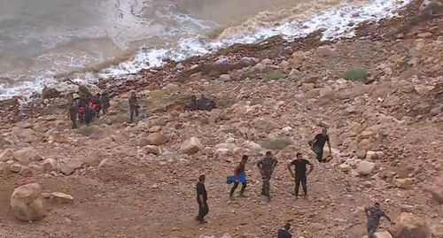 At least 18 people have been killed after flash floods swept away a group of teachers and students visiting hot springs near the Dead Sea.