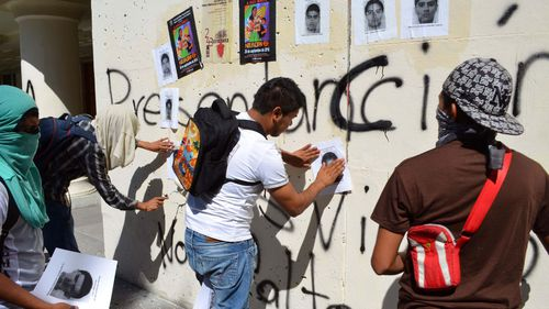 Protesting students paste images of the 43 missing students on the walls of the main Guerrero state courthouse in the city of Chilpancingo, Mexico in 2016.