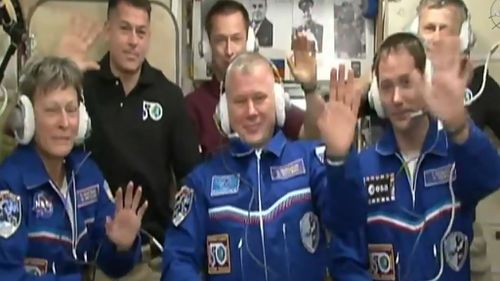 NASA astronaut Peggy Whitson, Oleg Novitskiy of the Russian space agency Roscosmos, and Frenchman Thomas Pesquet of the European Space Agency, wave after docking at the International Space Station. (AFP / NASA TV)
