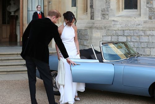 Prince Harry extends a gentlemanly gesture his new wife. Picture: AP