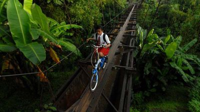 A 100-foot bridge barely wider than a bike tyre spanning a bridge in Java may very well be the world's most dangerous school run. (All images Getty)