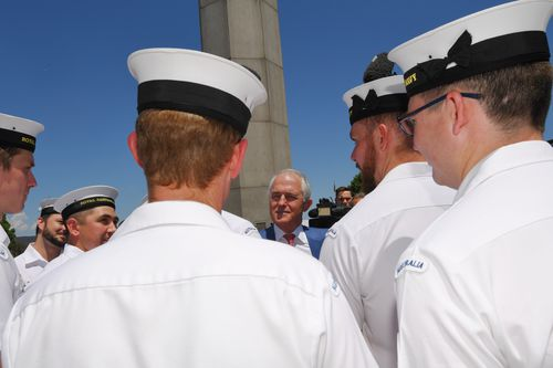 Mr Turnbull speaks to naval officers after the announcement of the winning bid to build the offshore patrol vessels. (AAP)