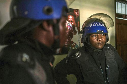 Riot police raid the opposition Movement for Democratic Change (MDC) headquarters in Harare Thursday, Aug. 2, 2018. MDC leader Nelson Chamisa says police have raided the headquarters and seized computers, while police say 18 people there were arrested. The developments come a few hours before the electoral commission is expected to start releasing the results of Monday's presidential election. (AP Photo/Mujahid Safodien)