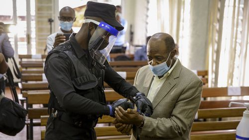 "A policeman handcuffs Paul Rusesabagina, right, whose story inspired the film ""Hotel Rwanda"", before leading him out of the Kicukiro Primary Court in the capital Kigali, Rwanda Monday, Sept. 14, 2020"